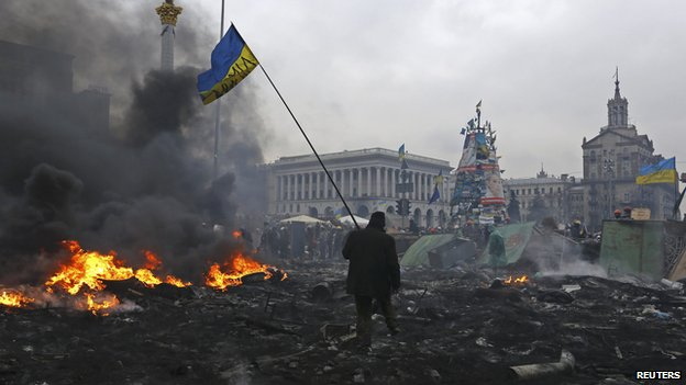 Anti-government protester carrying the national flag through Independence Square in Kiev, Feb 2014.