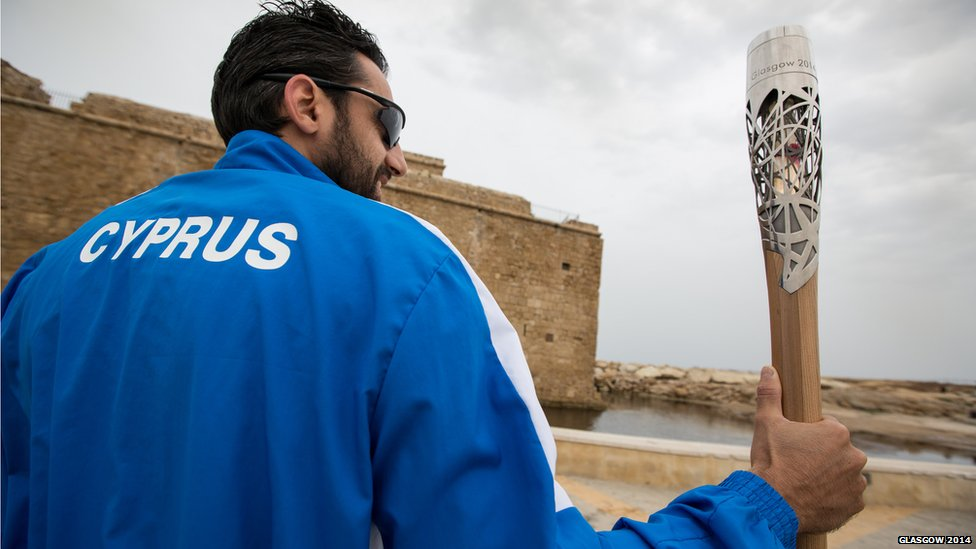 Man in a Cyprus team tracksuit holding the Queen's Baton.