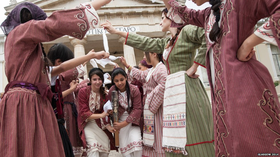 Dancers in traditional Cypriot costume perform with the Queen's Baton.
