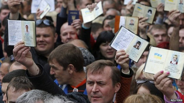 People waiting to vote in Moscow hold up Ukrainian passports