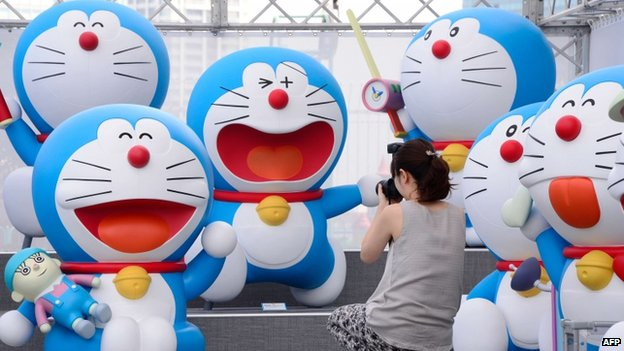 Life-size figures of Doraemon sit on the roof of the Tokyo Tower Foot Town on 18 July 2013