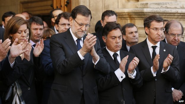 Popular Party's (PP) General Secretary Maria Dolores de Cospedal, Spain's Prime Minister Mariano Rajoy, Leon provincial council vice-president Marcos Martinez, Castilla and Galicia regional government president Alberto Nunez Feijoo applaud after observing a moment of silence outside the council building where the body of late Leon provincial council chief Isabel Carrasco lies in state in Leon on May 13