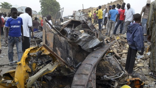 People look at damage in a market area after a bomb explosion in Ajilari-Gomari near Maiduguri's airport, Borno State, 2 March 2014