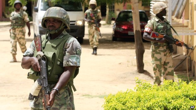 Nigerian soldiers stand guard at the offices of the state-run Nigerian Television Authority in Maiduguri, Nigeria - June 2013