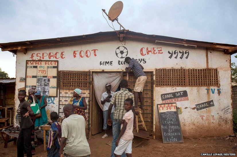 A man tries to fix the satellite equipment at a local public television hall in Petevo in the Central African Republic's capital of Bangui
