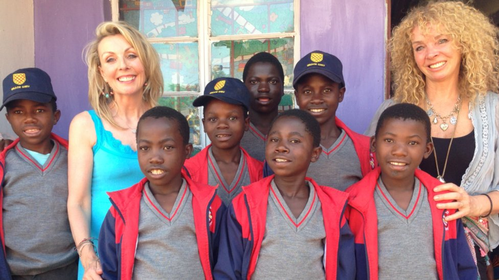 BBC East Midlands Today presenter Anne Davis pictured with Alice Pulford's mother Yvonne and orphaned boys in Malawi, Africa