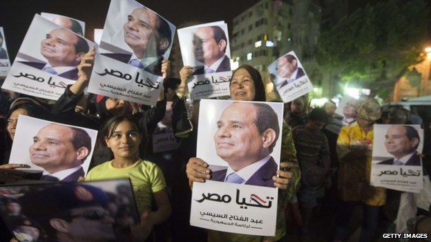 Supporters of Mr Sisi watch a screen in Cairo showing his first television interview