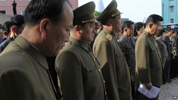 North Korean officials stand among the families of victims