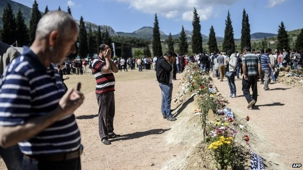 People mourn their relatives at the cemetery where some of the 301 people killed in the Soma disaster were buried, on May 18, 2014