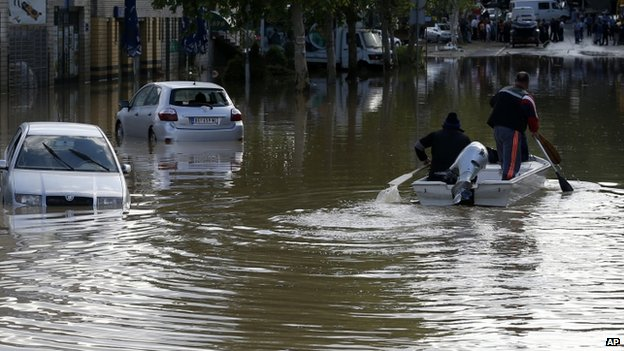 People paddle a boat down a flooded street in Obrenovac, some 30km (18 miles) south-west of Belgrade
