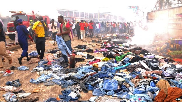 Stallkeepers salvage their belongings as rescuers and residents gather at the charred scene following a bomb blast at Terminus market in the central city of Jos (20 May 2014)