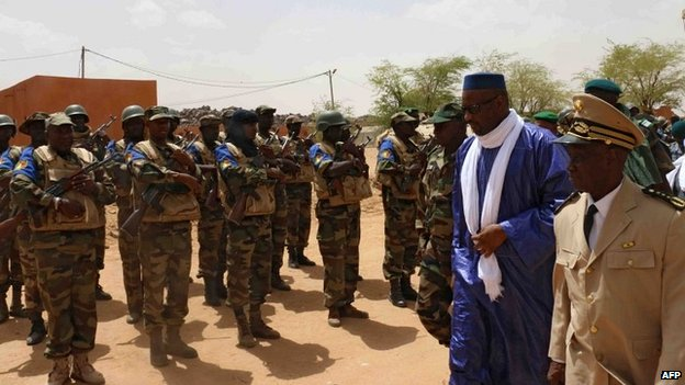 Mali's Prime Minister Moussa Mara reviews troops upon his arrival at Kidal, northern Mali, on May 17, 2014,