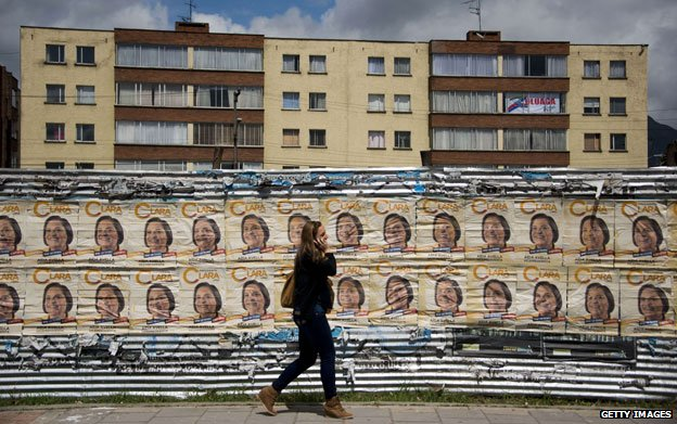 Woman walks past campaign posters for Clara Lopez