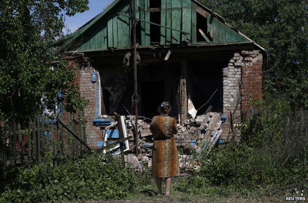 A woman looks at her ruined house near Sloviansk, Ukraine, 22 May