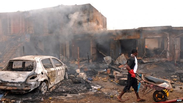 A boy pushes a wheelbarrow past the wreckage of a burnt vehicle and burning shops following a bomb blast at Terminus market in the central city of Jos on 20 May 2014 - an attack the authorities suspect was perpetrated by Boko Haram