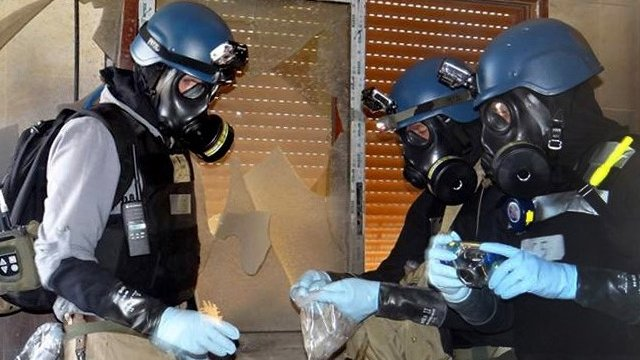 File photo - Members of the UN investigation team take samples from the ground in the Damascus countryside of Zamalka, Syria, on 29 August 2013