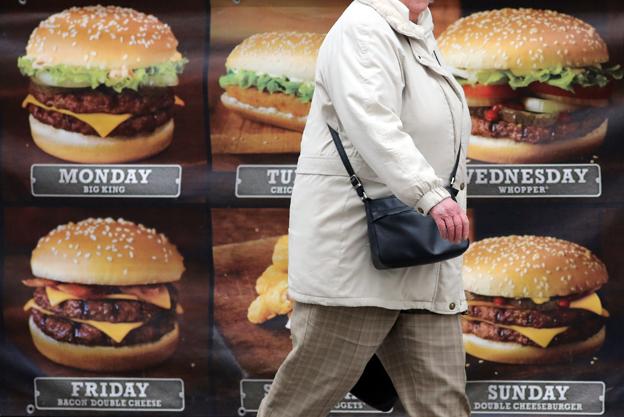 Woman walking past burger shop