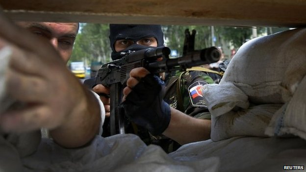 A pro-Russian rebel mans a newly erected barricade on the airport road in Donetsk, 27 May