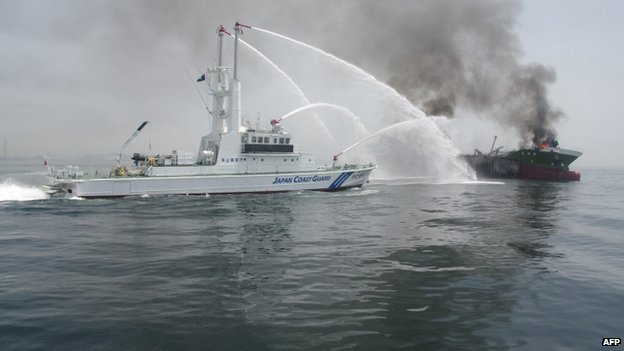 "This handout picture taken and released by Japan""s Coast Guard on 29 May 2014 shows a Coast Guard boat (L) fighting a fire onboard the 998-tonne oil tanker Shoko-Maru (R) off the coast of Hyogo prefecture, around 450 kilometres (280 miles) west of Tokyo"