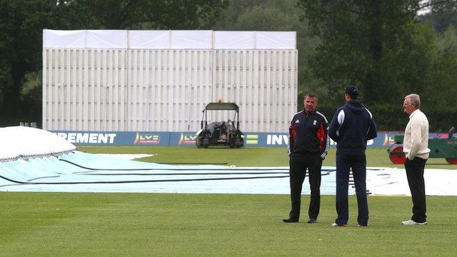 Umpires David Millns (l) and Steve Garrett (r) talk with Middlesex bowler Steven Finn