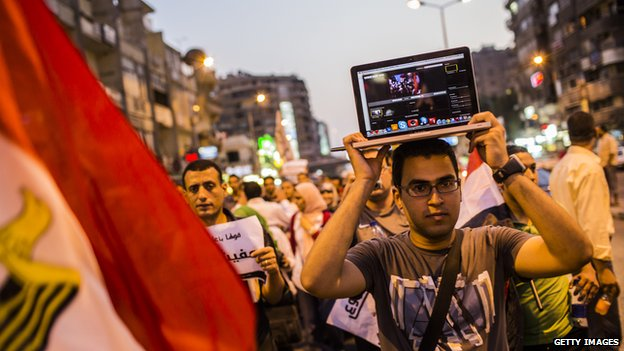 A Egyptian man holding a laptop on his head.