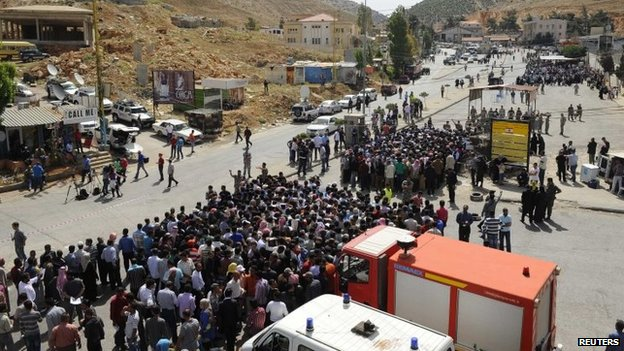 Syrians living in Lebanon line up as they wait to cross the Masnaa border crossing between Lebanon and Syria to vote in the presidential election June 3, 2014.