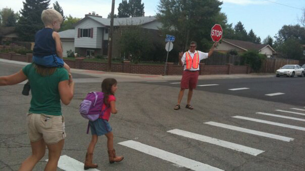 Crossing guard helps children across the street