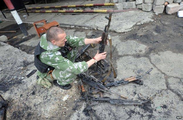 A rebel fighter examines abandoned guns inside the captured National Guard base in Luhansk, Ukraine, 4 June