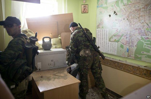 Rebel fighters inspect an office inside the border guard base in Luhansk, 4 June