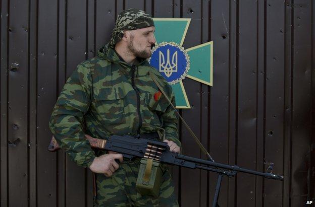 A rebel fighter guards the captured border guard base in Luhansk, 4 June