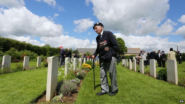 A member of the Normandy Veterans Association views headstones at Jerusalem Cemetery in Chouain, France, on 4 June 2014 at a commemorative ceremony to mark 70th anniversary of the D-Day landings