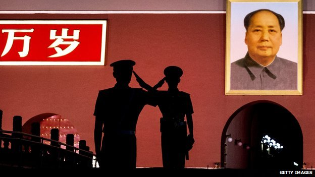 Chinese Paramilitary police officers salute each other as they stand guard below a portrait of the late leader Mao Zedong in Tiananmen Square on 4 June, 2014 in Beijing, China