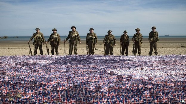 People in WW2 uniforms standing behind many small union flags on a beach