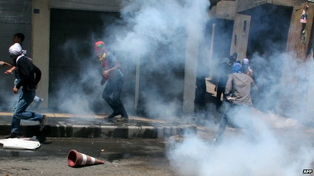 Kurdish protesters try to kick gas canisters away as they clash with riot police in Diyarbakir 08/06/2014
