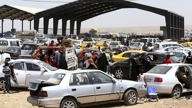 Families fleeing the violence in the Iraqi city of Mosul arrive at a checkpoint in outskirts of Irbil, in Iraq's Kurdistan region, on 10 June 2014