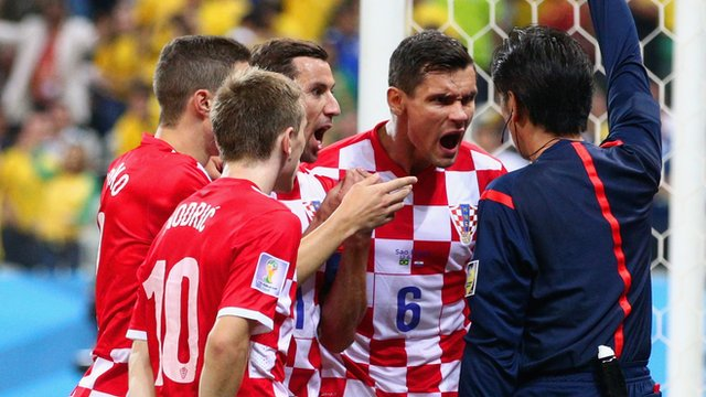 Croatia players argue with Referee Yuichi Nishimura