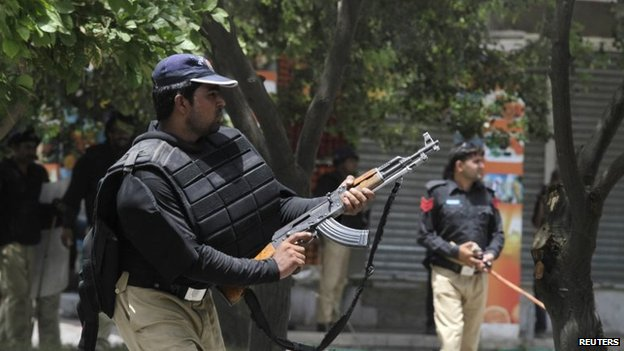A policeman fires with his gun to disperse the supporters of Tahirul Qadri during a protest in Lahore, 17 June 2014
