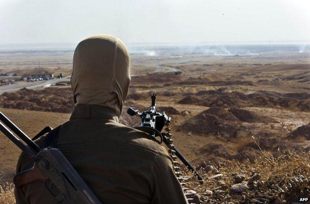 A Kurdish fighter monitors a road in Diyala province, Iraq, 14 June