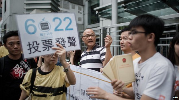Demonstrators supporting the Occupy Central movement display placards asking residents to cast ballots