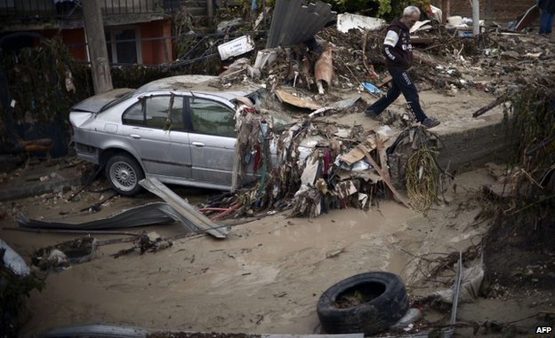 A man walks past a damaged car in a flooded street of a suburb of the Black Sea port of Varna (AFP)