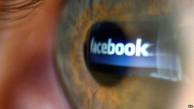 Facebook logo reflected on an eye