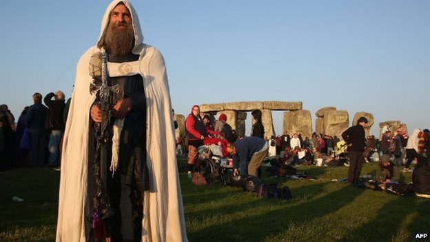 A modern druid named Merlin stands as the sun rises at the prehistoric monument Stonehenge