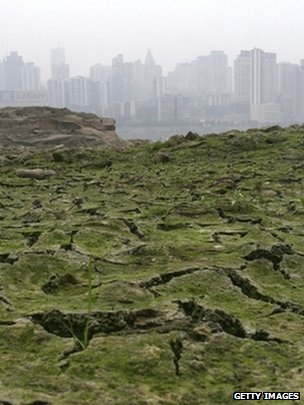 Dried river bed with Chinese city skyline in the background (Getty Images)