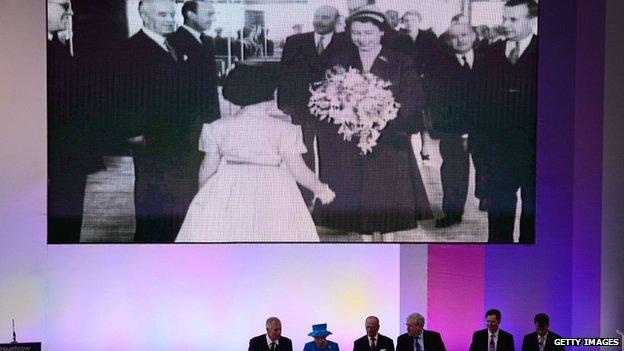 Queen Elizabeth II watches a video of herself opening the original terminal building in 1955