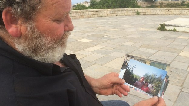 Nikos Britzolakis with pictures of his wife