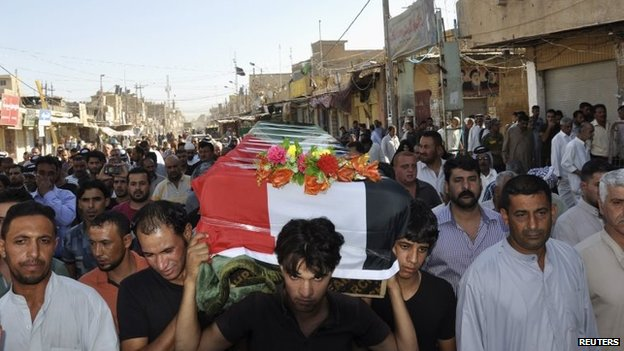 Mourners carry the coffin of a victim killed by a suicide bomb attack in Mahmoudiyah