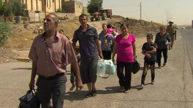 People walk away from Qaraqosh