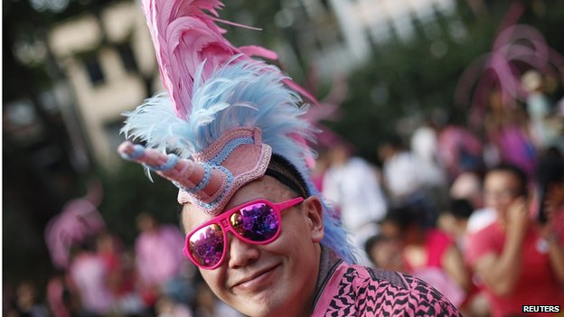 """A participant dressed in pink enjoys a picnic before taking part in the forming of a giant pink dot at the Speakers"""" Corner in Hong Lim Park in Singapore on 28 June 2014."""