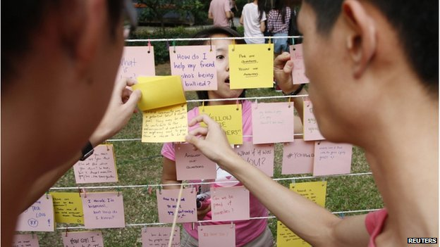 """Participants dressed in pink read about issues of the Lesbian, Gay, Bisexual and Transgender (LBGT) community at a question-and-answer area where participants are free to write their questions and answers, before taking part in the forming of a giant pink dot at the Speakers"""" Corner in Hong Lim Park in Singapore on 28 June 2014."""