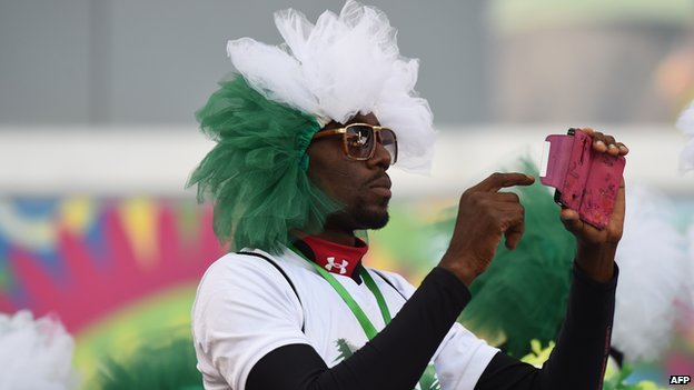 A Nigerian supporter takes a photograph ahead of the football match between Nigeria and Bosnia-Hercegovina on 21 June 2014